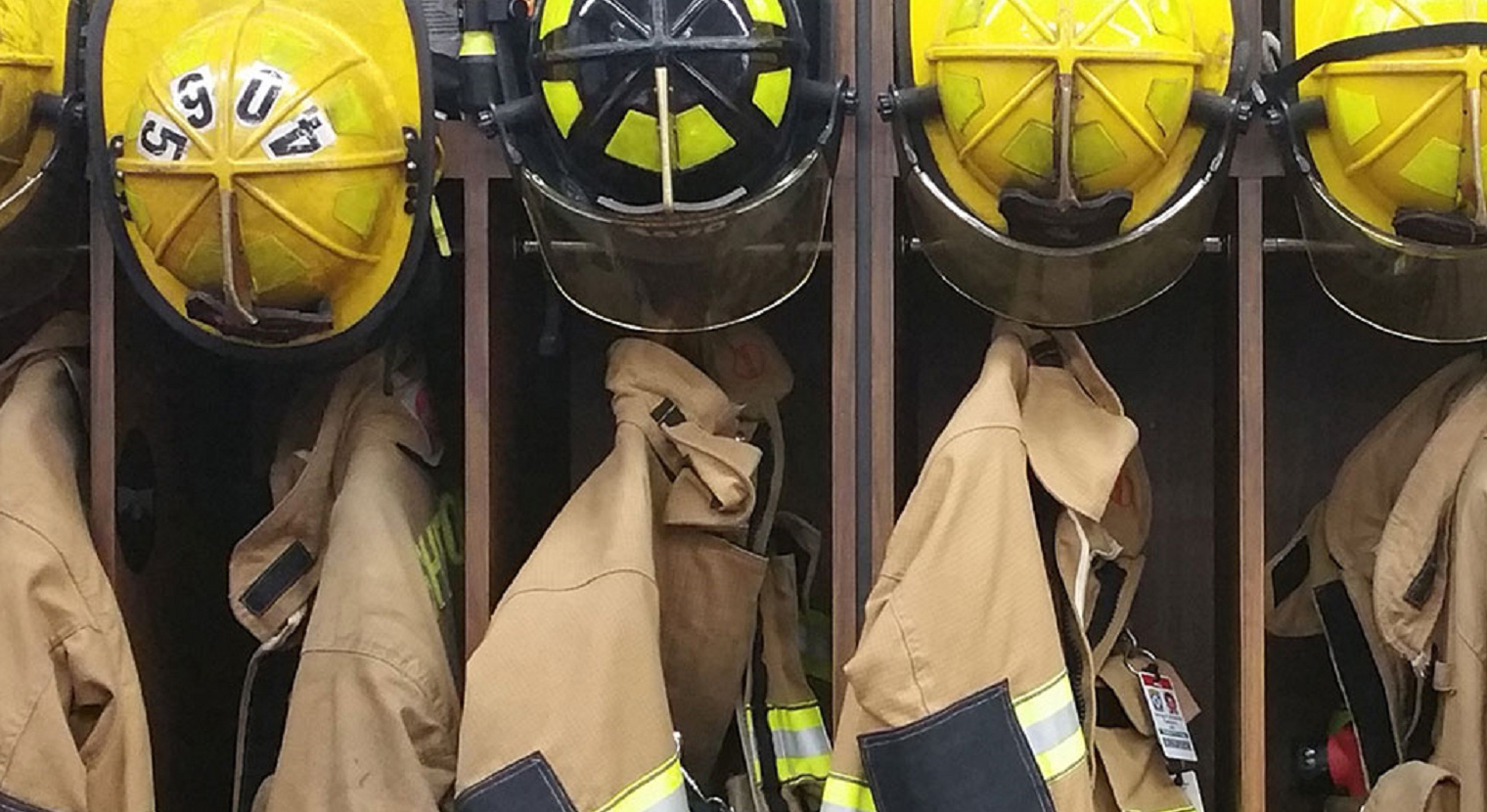 Firefighters' helmets and jackets hanging in a line