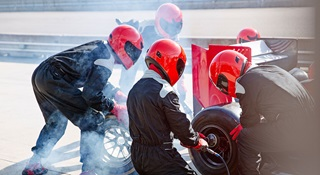 Engineers wearing red helmets changing a racing car tyre in a pit stop